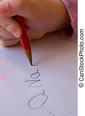 Child writing her name - A young child learning to write her...