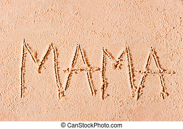 child wrote the word mom in the sand on the beach