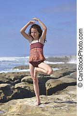 Child yoga pose - Young girl performs Vrksasana yoga tree...
