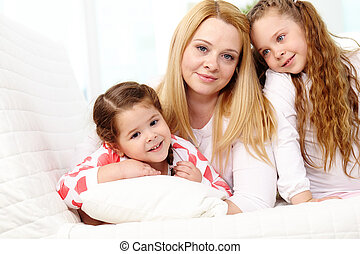 Loving mother with her two pretty daughters having rest at home