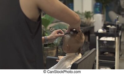 Childen hairstyle concept. Barber with shaving razor in male salon. Hairstylist using straight razor for shave hair little boy. Hairdresser doing boy hairdo in hairdressing salon.