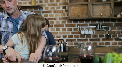 Childen Helping Parents With Cooking In Kitchen, Happy Mother Looking At Father With Two Kids Preparing Food At Home Talking