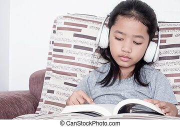 The little girl wore a white headset, sat on the couch and reading a book with intent.