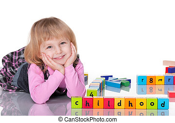 A cheerful laughing kid in pink is playing with blocks; isolated on the white background