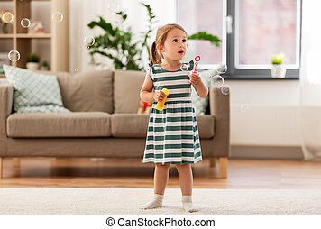 little girl blowing soap bubbles at home