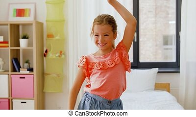 happy little girl dancing in her room at home