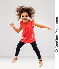 happy little african american girl jumping