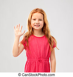 smiling red haired girl in pink dress waving hand