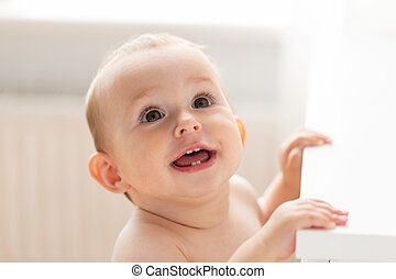 happy little baby boy or girl at home looking up