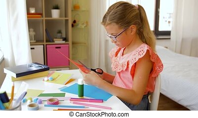 girl cutting color paper with scissors at home - childhood,...