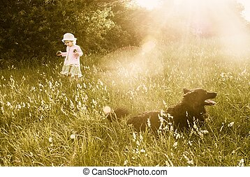 Cute little girl collecting cones under the protection of a dog