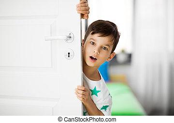 surprised little boy behind door at home