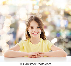 beautiful little girl sitting at table