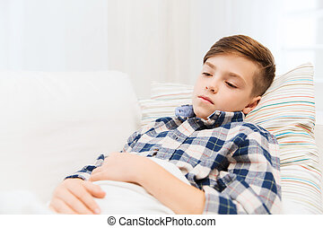 ill boy with flu lying in bed at home