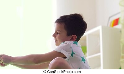 happy little boy playing with airplane toy at home -...