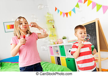 happy children blowing soap bubbles at home