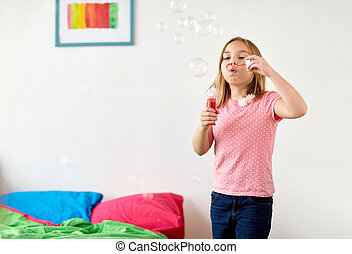 girl blowing soap bubbles at home
