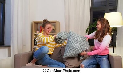 happy teenage having pillows fight at home - childhood, ...