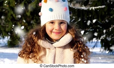 childhood, leisure and season concept - portrait of happy little girl in winter clothes outdoors over snow falling