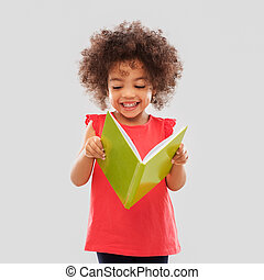 happy little african american girl reading book