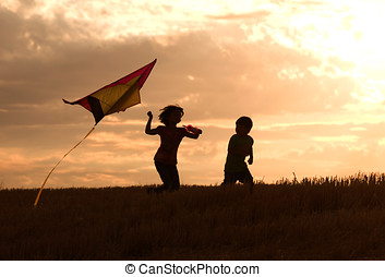 Childhood memories. - Two kids flying a kite at sunset...