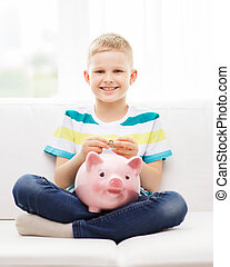 childhood, money, investment and happy people concept - smiling little boy with piggy bank and money at home