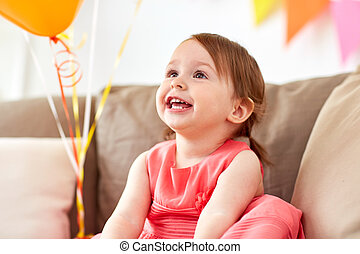 happy baby girl on birthday party at home