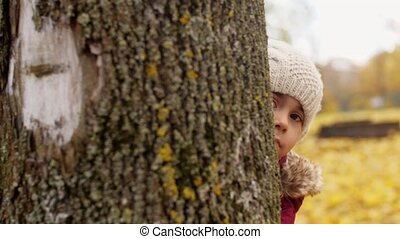 beautiful little girl hiding behind tree in autumn -...