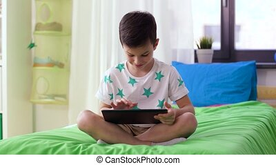 smiling boy with tablet pc computer at home - childhood,...