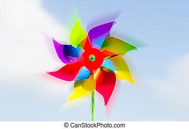 Childish pinwheel against blue sky in motion.