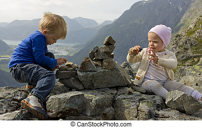 Children (1 and 3 years old) building a cairn on a mountaintop. Rauma, Molde