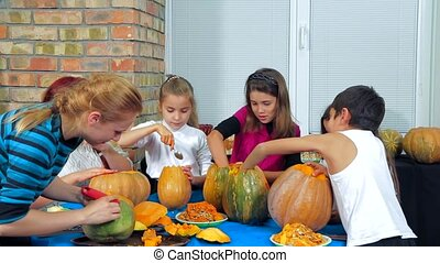 Children And Adults Cleaning Halloween Pumpkins