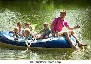 Children and adults float on an inflatable boat and fish a...
