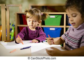 Children and fun, two preschoolers drawing in kindergarten