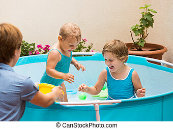 Children and mother playing with balls in pool