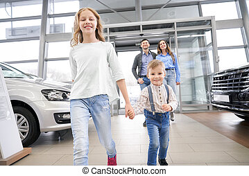 Children and parents walking in car center showroom.