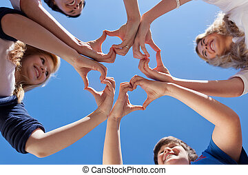Children And Teacher Forming Hearts Against Blue Sky