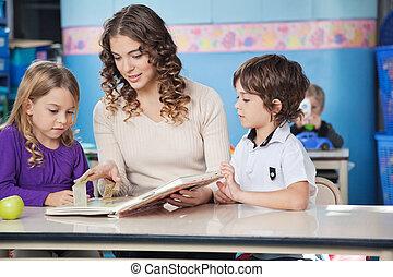 Children And Teacher Reading Book In Preschool