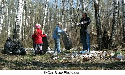 Children and their father collect trash to garbage bags in...