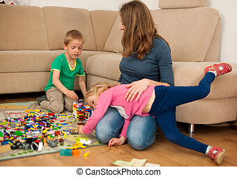 Children and their mother are playing with blocks on the ground in living room