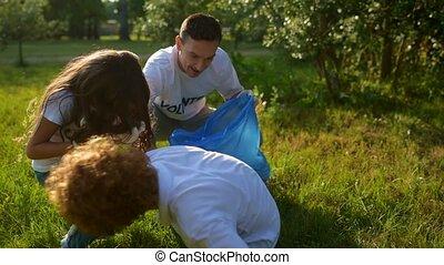 Children and volunteers collecting litter outdoors -...