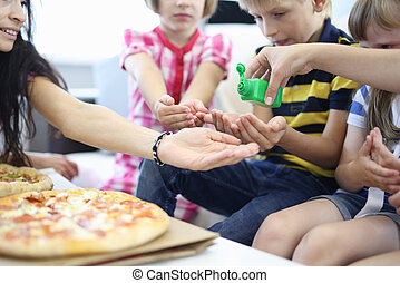 Children and woman are sitting on couch and treating their hands with disinfectant next to pizza.