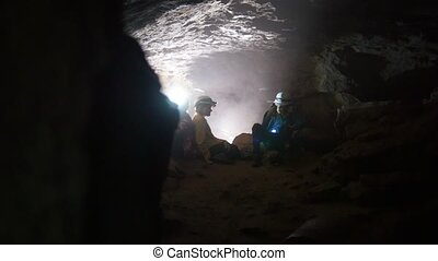 Children are considering and sitting in the cave undeground,...