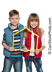 Children are holding model of a house