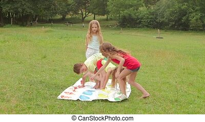 Children are playing a twister in the garden. Slow motion