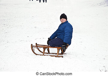 children are skating at a toboggan run in winter on snow