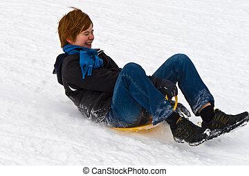 children are sledding down the hill in snow, white winter -...