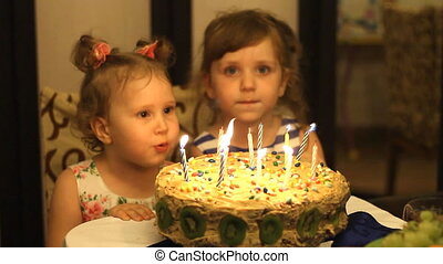 Children are smiling and laughing at the cake with candles.