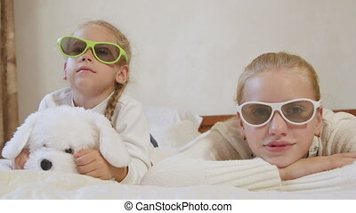 Children are watching 3d tv with glasses on the bed