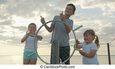 Children at an imaginary steering wheel at sunset. Happy childhood